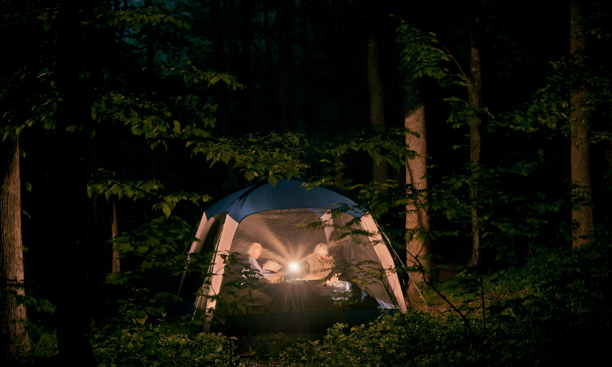 Chiaroscuro in the forest: couple reading by lantern light, Cosby Campground, Great Smoky Mountains National Park, Tennessee